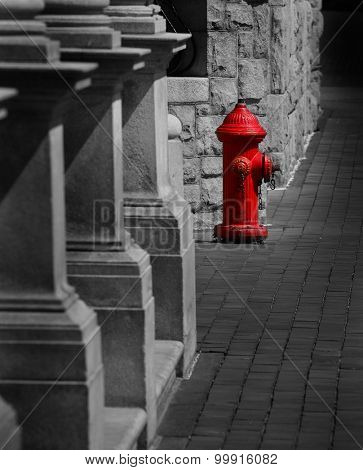 Red fire hydrant on sidewalk next to old stone building