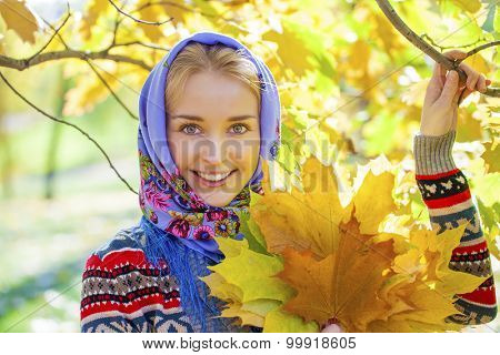 Portrait close up of young beautiful woman, on background autumn park