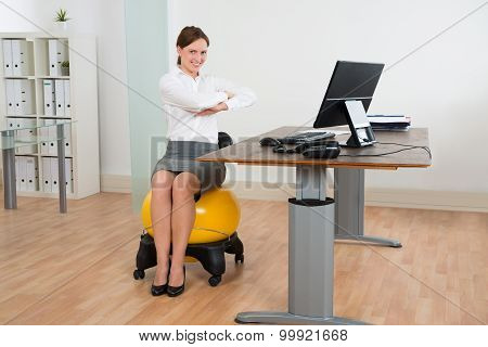 Businesswoman Exercising On Pilates Ball