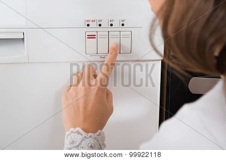 Person Hands On Button Of Dishwasher