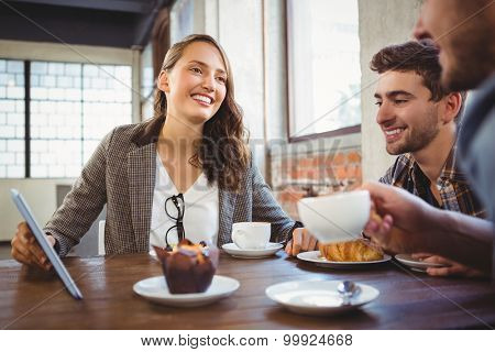 Smiling friends enjoying coffee and using at tablet at coffee shop