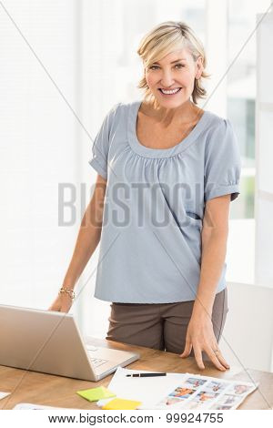Portrait of a smiling designer working on a photo catalog at office