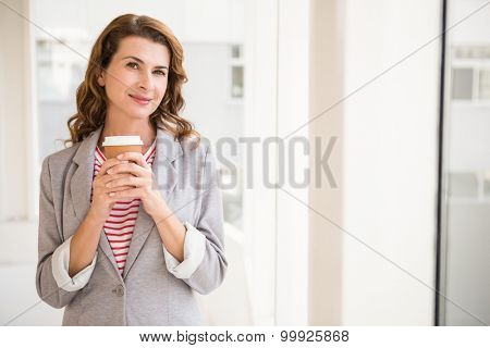 Portrait of smiling casual businesswoman holding take-away cup in the office