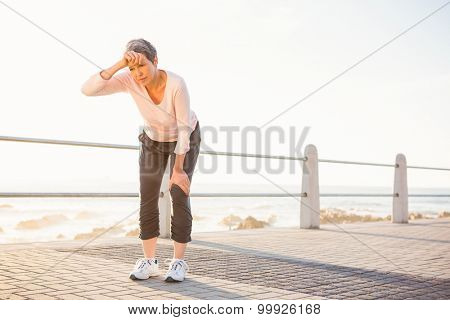 Sweating sporty woman resting at promenade on a sunny day