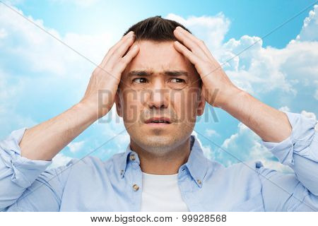 stress, headache, health care and people concept - unhappy man with closed eyes touching his forehead over blue sky and clouds background