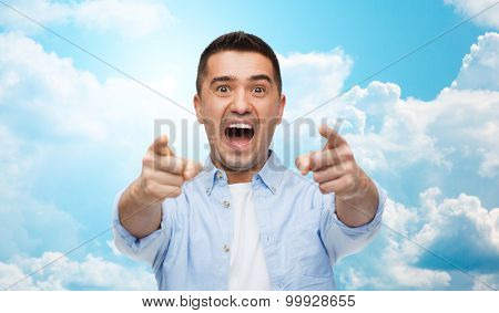anger, fear, emotions, gesture and people concept - angry or scared man shouting and pointing finger on you over blue sky and clouds background