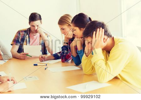education, school, test and people concept - group of students with papers thinking or making test