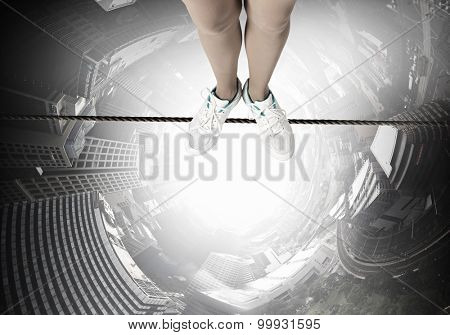Top view of person standing on rope above city
