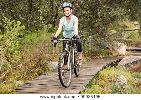 Smiling fit woman cycling her bike on a wooden path