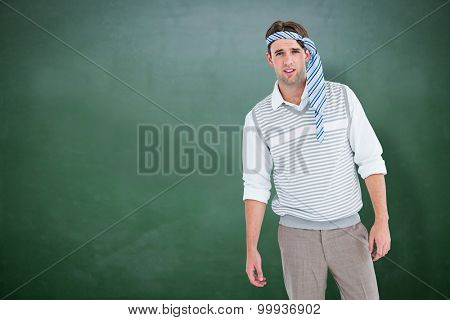 Geeky man with tie on his head against green chalkboard