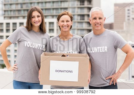 Portrait of smiling volunteers holding donation box on roof of building