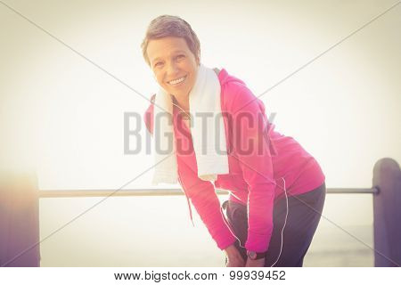 Portrait of smiling sporty woman listening to music at promenade