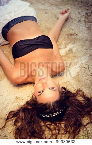 Provocative sexi brunette in black bra on sandy dry ground