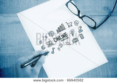 Left hand writing on white page on working desk against online marketing