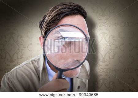 Spy looking through magnifier against elegant patterned wallpaper in neutral tones