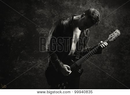Shirtless Man in leather jacket Playing Guitar