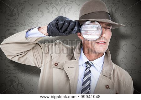 Spy looking through magnifier against elegant patterned wallpaper in grey tones