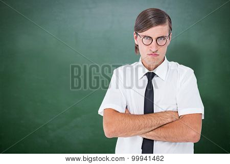 Geeky businessman looking at camera with arms crossed against green chalkboard