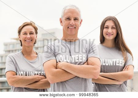 Portrait of smiling volunteers with arms crossed on roof of building