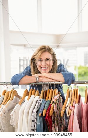 Portrait of smiling woman leaning on clothes rail in clothing store