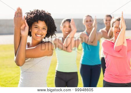Portrait of smiling sporty women doing eagle pose in yoga class in parkland