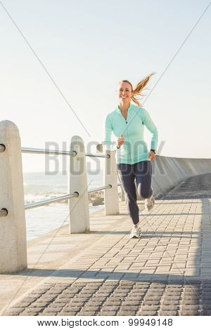 Smiling fit blonde jogging at promenade on a sunny day