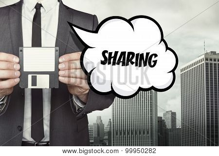 Sharing text on speech bubble with businessman holding diskette