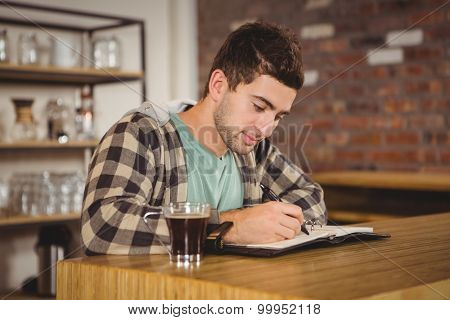 Hipster having coffee and writing in planner at coffee shop