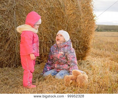 Children Playing With A Soft Toy Near Haystacks