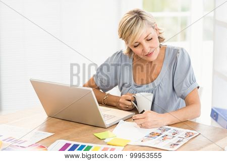Attentive designer looking a photo catalog at office