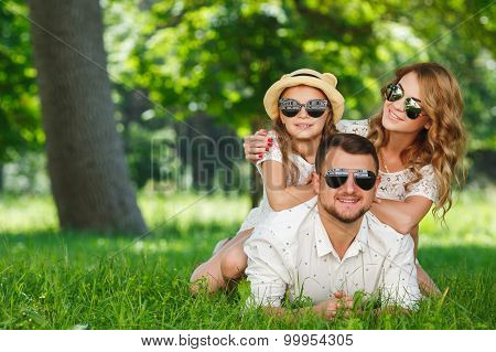 Happy young family spending time together outside in green nature