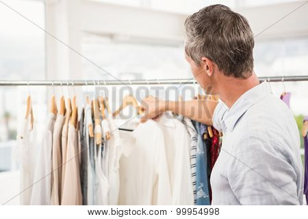 Rear view of man browsing clothes in clothing store