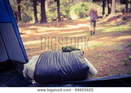 Sleeping bag in front of blonde camper walking away in the nature