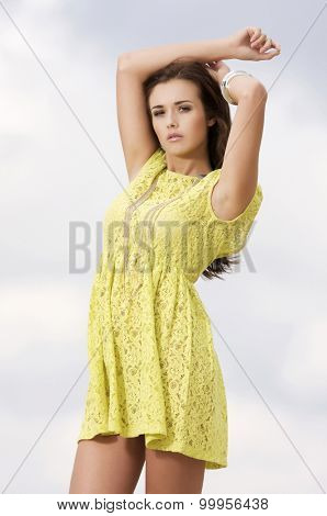 portrait of beautiful young adult attractive sexy and sensuality active pretty  brunette woman in yellow elegance dress on background blue sky
