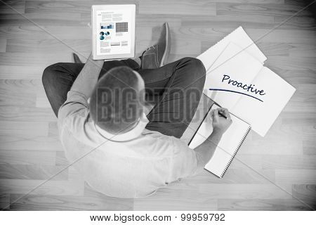 The word proactive and business stats against young creative businessman looking at tablet