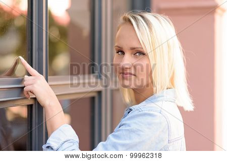 Pretty Blond Woman Pointing To A Window