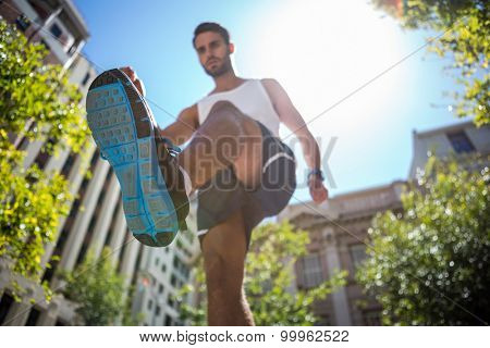 Low angle view of an athlete running in the street on a sunny day