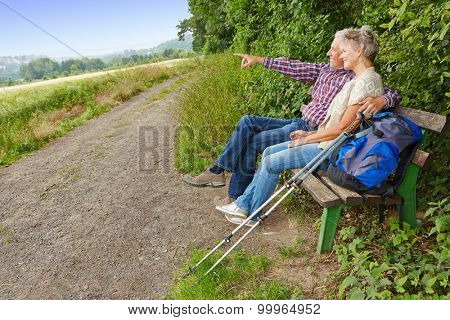Senior couple searching goal in the distance while sitting on a bench