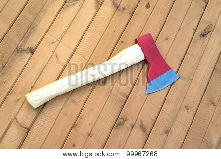 Ax with red blade on wooden surface