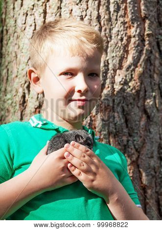 Portrait Of A Boy With Grey Chinchilla On His Hands