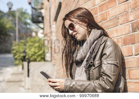 girl texting on her cell phone with urban wall on the back