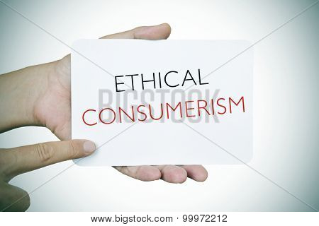closeup of a young caucasian man pointing his finger at a signboard with the text ethical consumerism, slight vignette added