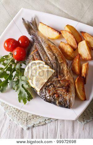 Grilled Dorado Fish With Fried Potatoes And Tomato Close-up