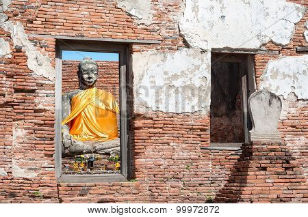 Buddha Statue With Orange Sash Seen Through The Window Of A Ruined Building At  Wat Worachet Tharam,