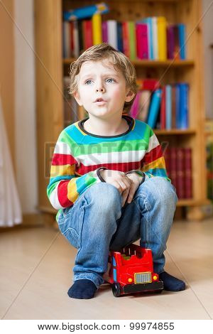Little Blond Kid Boy Playing With Wooden Toy Bus, Indoors