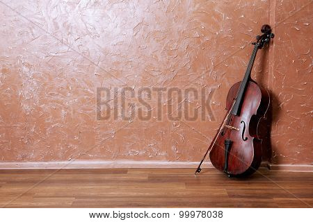 Classical cello and bow on brown wall background