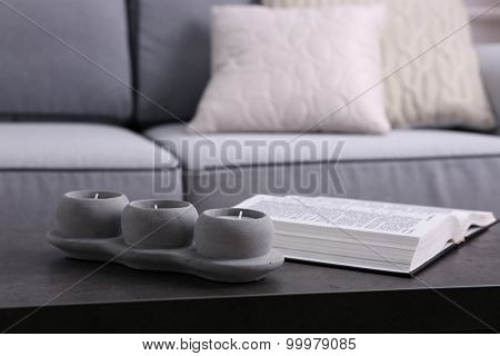 Book and candlestick on table on Modern sofa  background