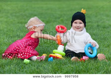 Portrait Of Two Pretty Little Girls Playing On The Grass