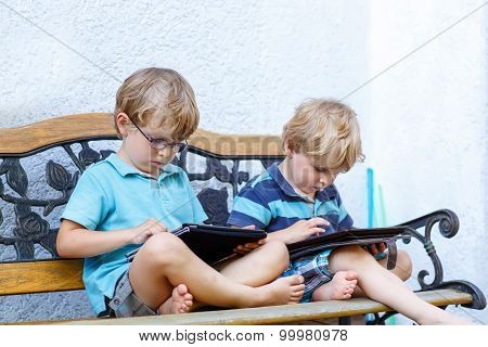Two Happy Little Boy Friends Holding Tablet Pc, Outdoors.
