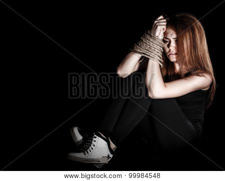 Beautiful Young Woman With Tied Arms Sitting On The Floor